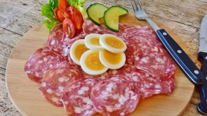 Sliced sausage, eggs, and some vegetables are arranged in a circle atop a wooden plate