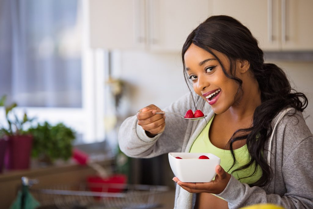 A smiling woman, holding a bowl filled with berries and a spoon filled with 2 spoons, ready to eat.