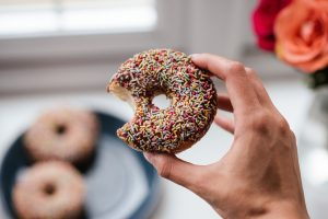 A hand holding a donut covered in chocolate and sprinklesthat has been bitten out of.