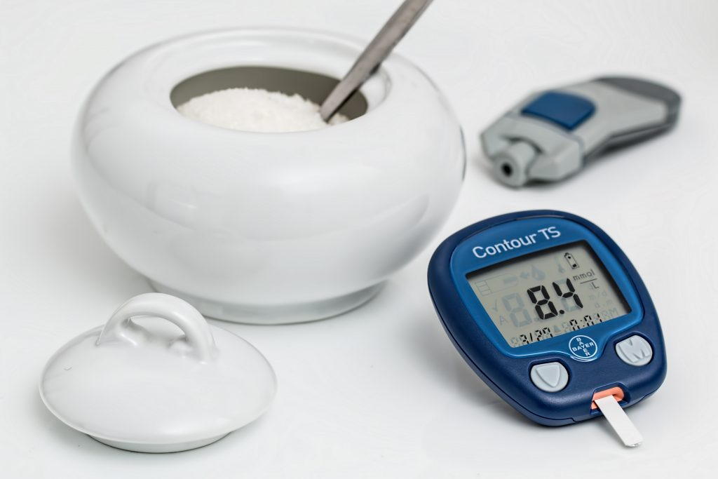 A white bowl filled with sugar with a spoon inside sitting next to a glucose monitor. Monitor reads 84.