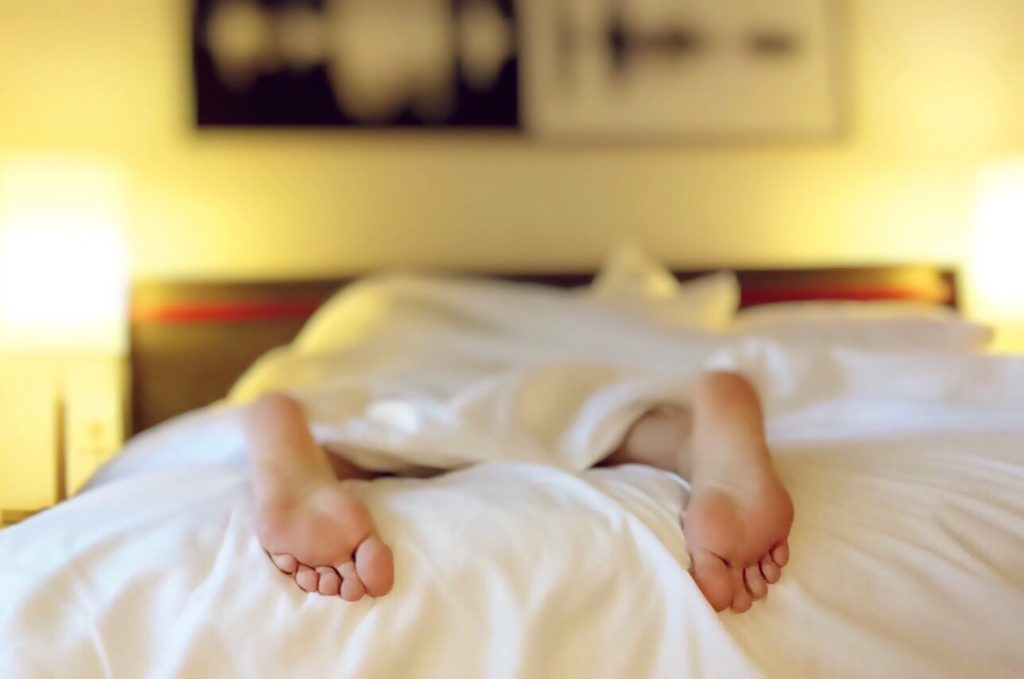 A photo of a person laying face down on the bed under the sheets with their feet showing from the bottom edge of the bed.